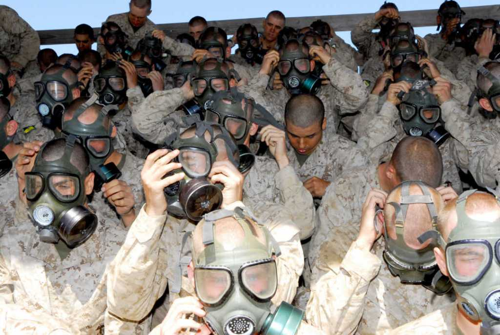 Company E recruits fit their gas masks on their heads to ensure a proper fit before going into the confidence chamber during field training at Edson Range, Camp Pendleton, Calif. The confidence chamber is designed to build the recruits' confidence in their gas masks.