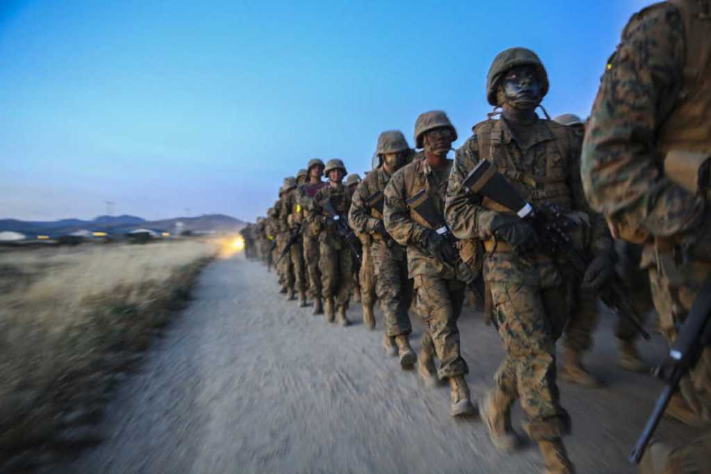 Recruits of Golf Company, 2nd Recruit Training Battalion, push through adversity to carry an ammunition can during the resupply hike at Edson Range, Marine Corps Base Camp Pendleton.