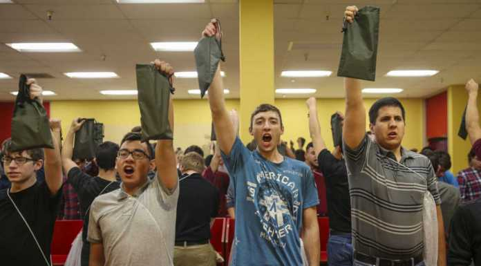 Recruits from Bravo Company, 1st Recruit Training Battalion, hold up their money valuable bags during receiving at Marine Corps Recruit Depot San Diego.
